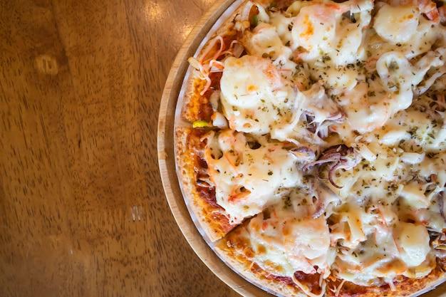 Pizza de frutos do mar em uma bandeja de madeira