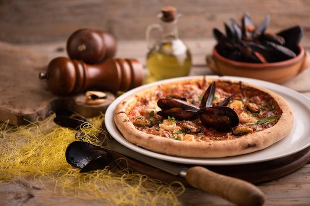 Pizza de frutos do mar em uma mesa de madeira rústica de perto