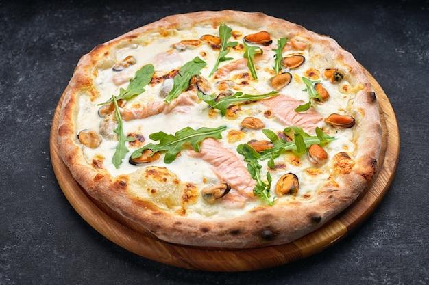 Pizza de frutos do mar, marinara, di mare, com salmão, mexilhões e rúcula, em uma placa de madeira, contra uma mesa escura