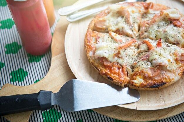 Pizza de frutos do mar que combinada com porcaria de camarão e lula na placa de madeira e pá de pizza