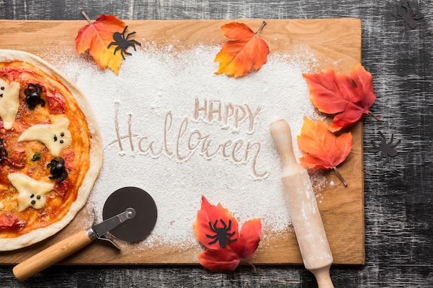Pizza de halloween com folhas na placa de madeira