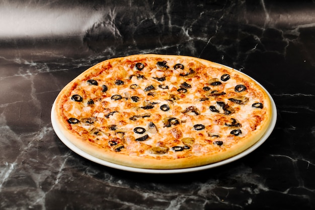 Pizza de ingredientes misturados com rolos de azeitona preta.