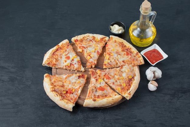 Pizza de mussarela quente fatiada na placa de madeira com óleo de alho e molho.