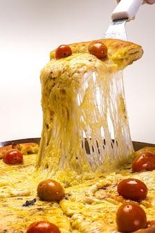Pizza de mussarela tradicional sendo cortada e retirada com a espátula com o queijo derretido sobre fundo branco.