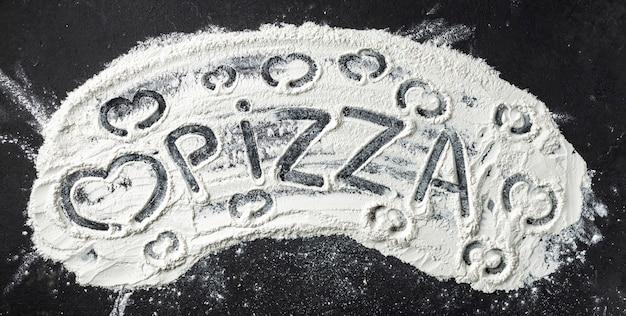 Pizza de palavra e coração são escritos em farinha, vista superior. fundo abstrato de cozimento