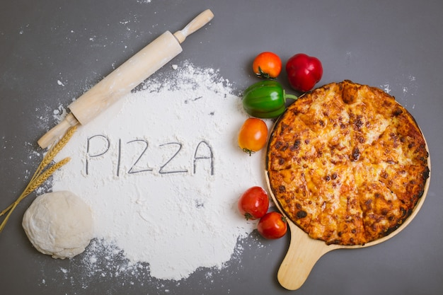 Pizza de palavra escrita na farinha com uma pizza saborosa