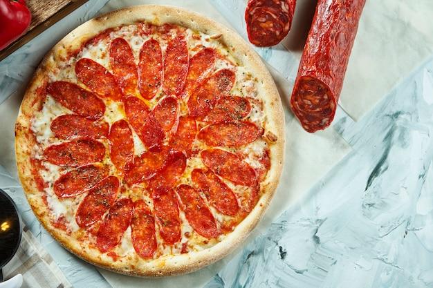 Pizza de pepperoni assada no forno com molho de tomate, queijo, salame, vermelho. composição com pizza crocante, tomate ... vista superior