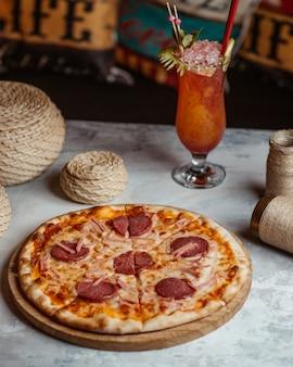 Pizza de pepperoni em uma placa de madeira com um copo de coquetel.