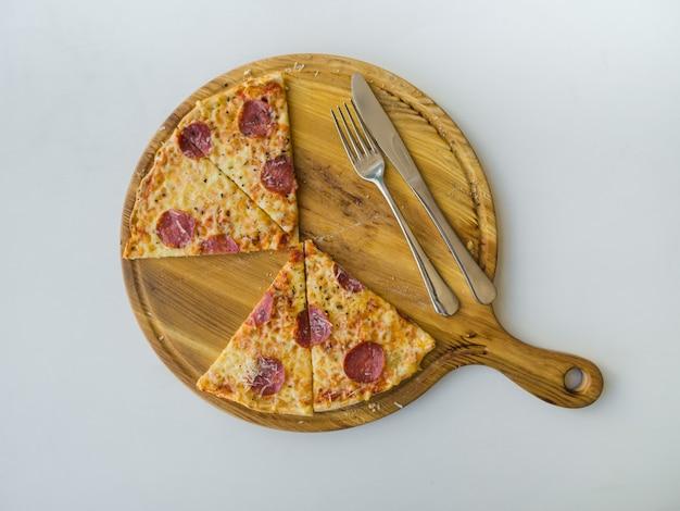 Pizza de pepperoni fatiada na mesa branca. vista do topo.