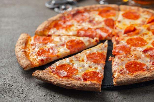 Pizza de pepperoni quente cortada em um fundo marrom.