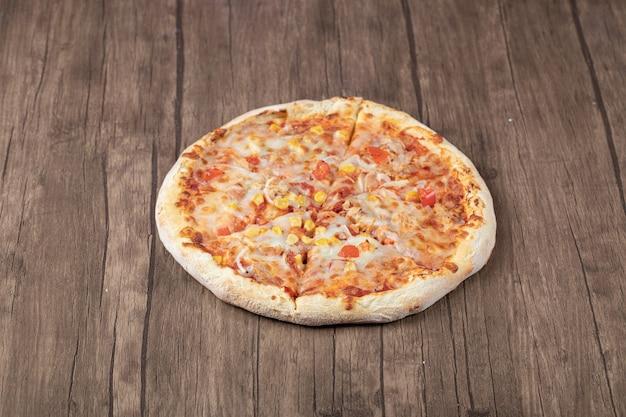 Pizza de pepperoni quente na mesa de madeira.