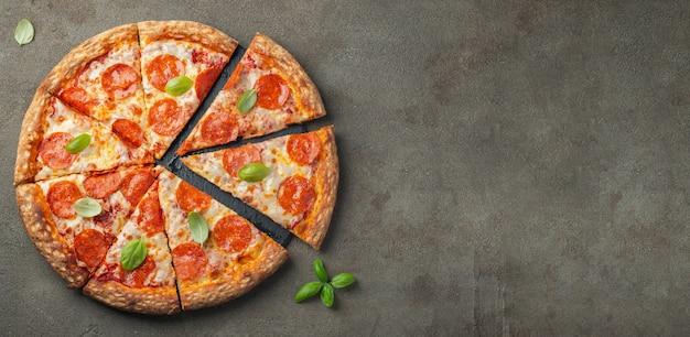 Pizza de pepperoni saborosa com manjericão na mesa de concreta