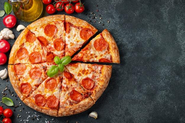 Pizza de pepperoni saborosa e ingredientes de cozinha