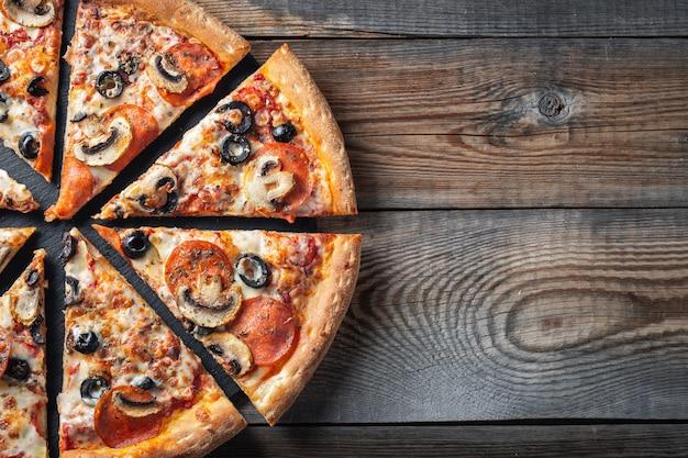 Pizza de pepperoni saboroso com cogumelos e azeitonas.