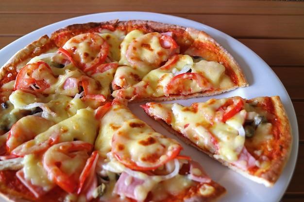 Pizza de presunto e tomate em um prato branco servido na mesa de madeira