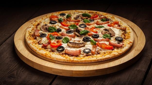 Pizza de presunto na mesa de madeira
