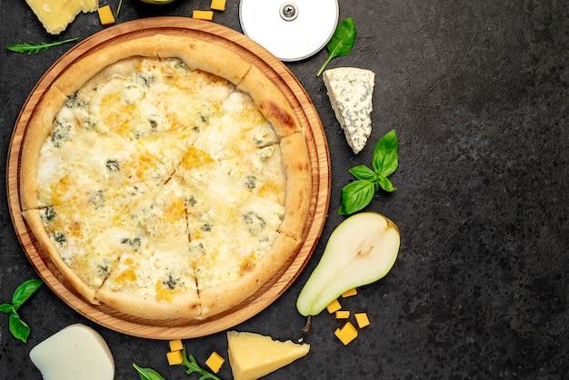 Pizza de quatro queijos com ingredientes em fundo de pedra com espaço de cópia para o seu texto