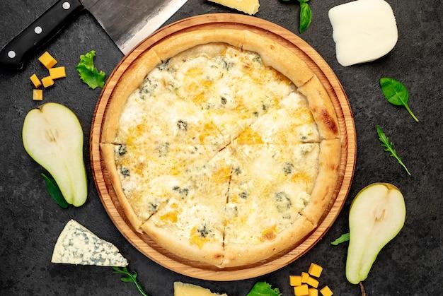 Pizza de quatro queijos com ingredientes em fundo de pedra