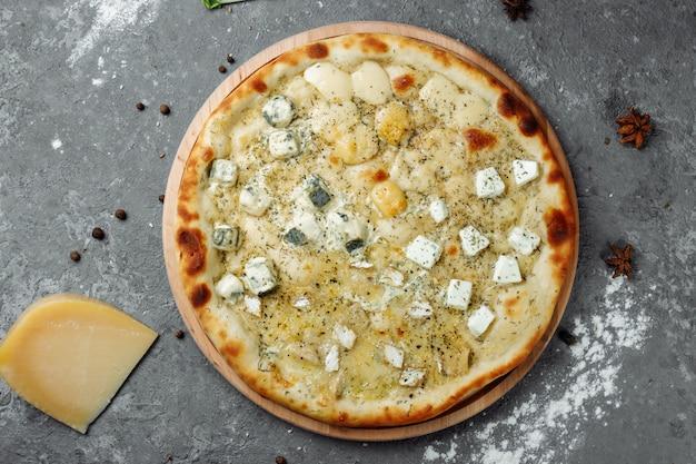 Pizza de quatro queijos, pizza italiana. pizza recheada com quatro variedades de queijo em um fundo cinza.