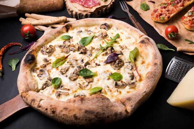 Pizza de queijo delicioso cogumelo saudável rodeado com ingredientes alimentares italianos