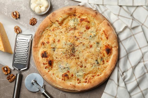 Pizza de queijo e ingredientes para cozinhar no cinza