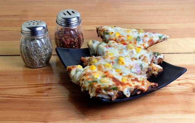 Pizza de queijo milho na mesa de madeira