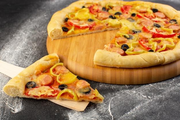 Pizza de queijo saborosa vista frontal perto com tomate vermelho, azeitonas pretas, pimentão e salsichas na mesa escura