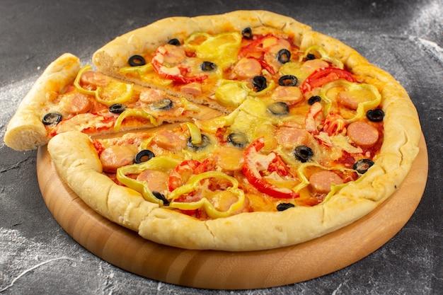 Pizza de queijo saborosa vista frontal perto com tomate vermelho, azeitonas pretas, pimentão e salsichas na superfície escura