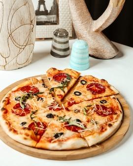 Pizza de salame vista frontal em uma placa de madeira