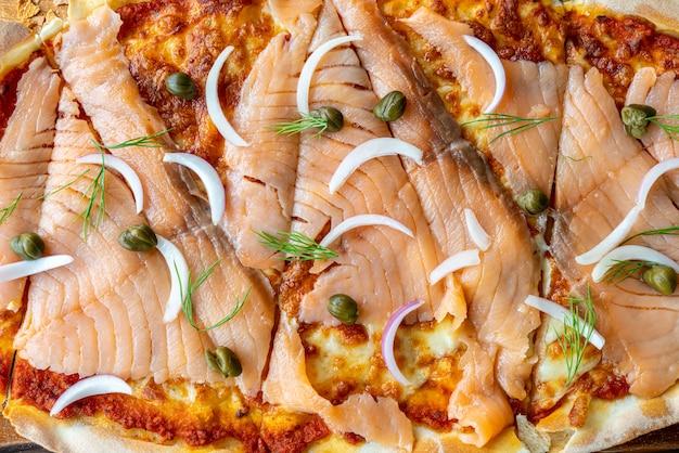 Pizza de salmão defumado na placa de madeira