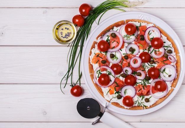Pizza de salmão escandinava com creme de queijo, alcaparras, tomate e cebola.