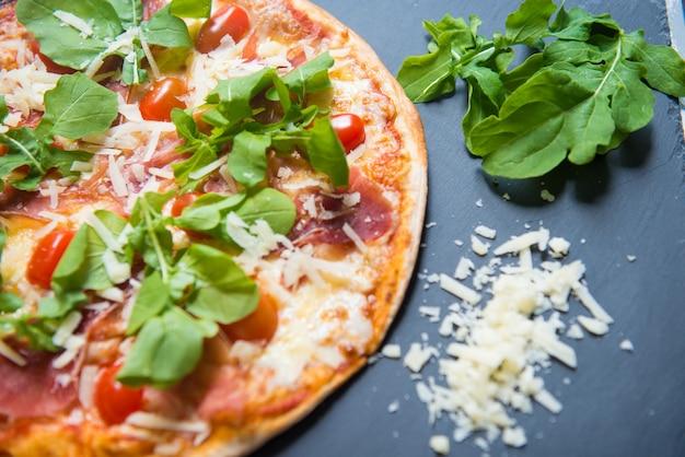 Pizza de tomate com presunto e manjericão fresco