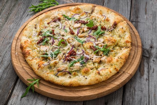 Pizza de tomate seco, presunto, rúcula e queijo parmesão