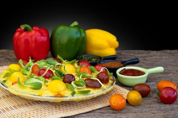 Pizza de vegetais caseira com tomate cereja e pimentão e outros ingredientes em um fundo de madeira
