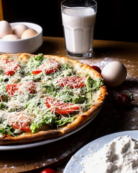 Pizza de vista lateral com tomates com ovos, um copo de leite e farinha em cima da mesa
