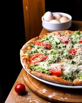 Pizza de vista lateral com tomates e ovos em cima da mesa