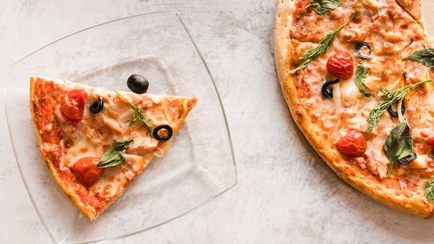 Pizza de vista superior com fatia em um prato