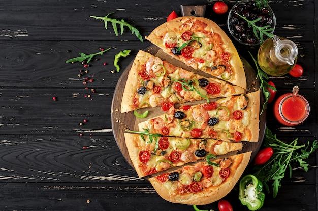 Pizza deliciosa de camarões e mexilhões de frutos do mar em uma mesa de madeira preta. comida italiana.