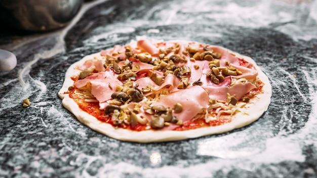 Pizza deliciosa preparada para ser cozida. fechar-se.