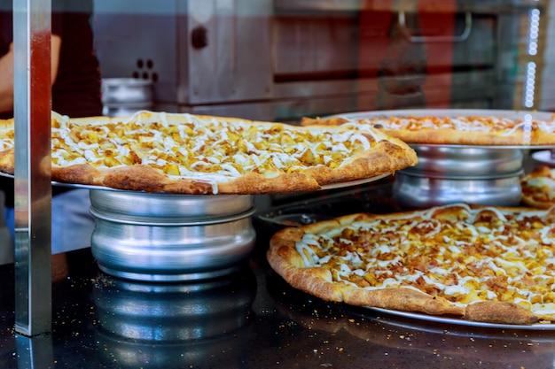 Pizza descansando em um balcão de pizzaria o fundo é restaurante