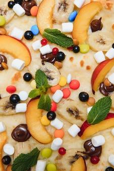 Pizza doce com molho de marshmallow e doces coloridos, pizza de chocolate com doces coloridos e pizza de chocolate com banana em um fundo branco