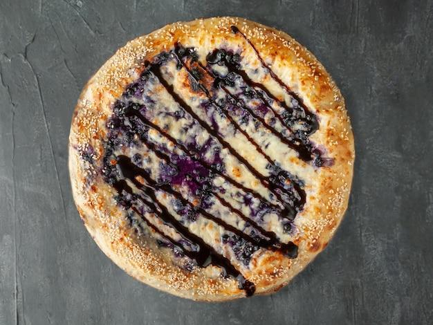 Pizza doce. mirtilos, cream cheese, mussarela e sulguni, com cobertura de chocolate. lado largo. vista de cima. sobre um fundo cinza de concreto. isolado.