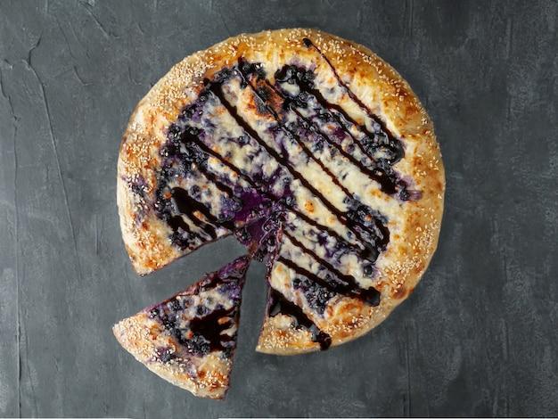 Pizza doce. mirtilos, cream cheese, mussarela e sulguni, com cobertura de chocolate. um pedaço é cortado da pizza. vista de cima. sobre um fundo cinza de concreto. isolado.