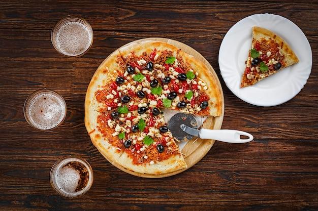 Pizza e cerveja em uma mesa de madeira em um pub, pizzaria ou bar de esportes. vista do topo.
