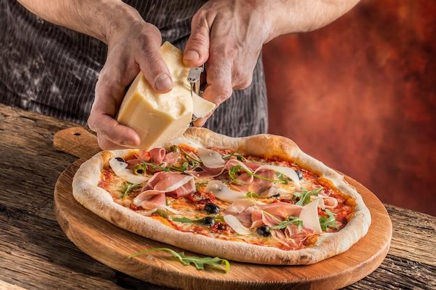 Pizza e chef. o chef do restaurante prepara uma pizza e a decora com queijo parmesão.