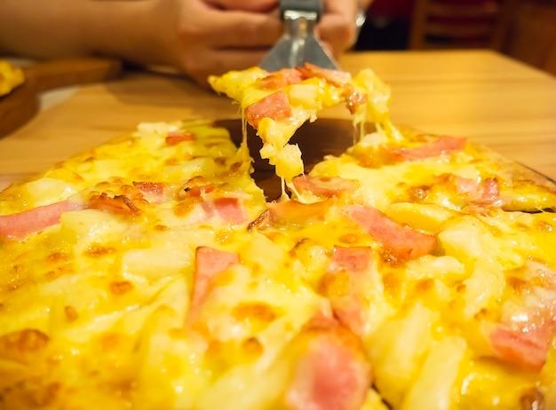 Pizza e colher de levantador com a mão