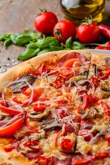Pizza e ingredientes picantes mexicanos em uma tabela de madeira. cozinha italiana tradicional. comida de festa