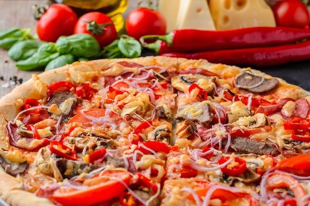 Pizza e ingredientes picantes mexicanos em uma tabela de madeira.