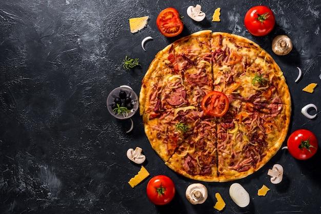 Pizza e ingredientes vegetarianos italianos perto dele
