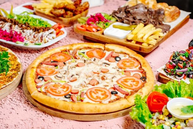 Pizza e outros alimentos na mesa